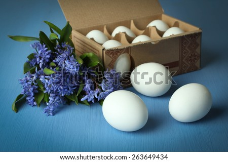 White chicken eggs in an egg box with flowers (Scilla) on a blue wooden background - stock photo