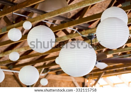 White Chinese paper lanterns hung in a barn as diy wedding reception decor. - stock photo