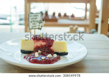 white chocolate cheesecake and raspberry sauce in coffee shop - stock photo