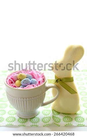 White chocolate Easter bunny with eggs in nest - stock photo