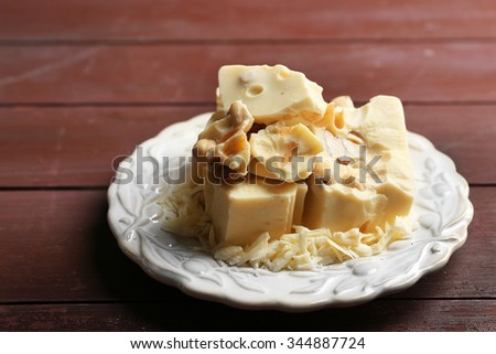 White chocolate pieces with nuts on plate, on color wooden background - stock photo