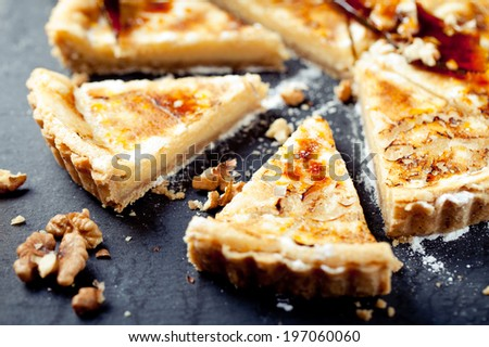 White chocolate, rum and caramel tart on a stone plate on a wooden background - stock photo