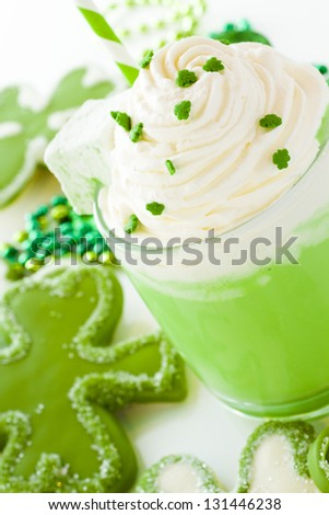 White chocolate shorrbread cookies in shape of four clover leaf with green hot chocolate.