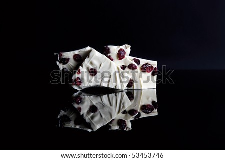 White chocolate with cranberries on black background - stock photo