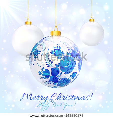 White christmas ball with blue floral ornament and golden ribbon