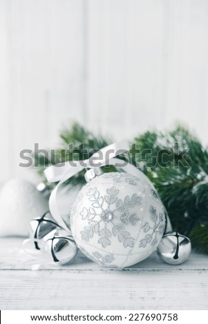 White christmas balls and fir branches with decorations on light background - stock photo