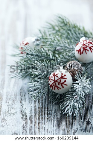 White christmas balls and spruce branch on a wooden background - stock photo
