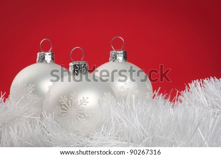 White Christmas baubles over red background