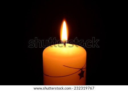 White christmas candle burning on a black background