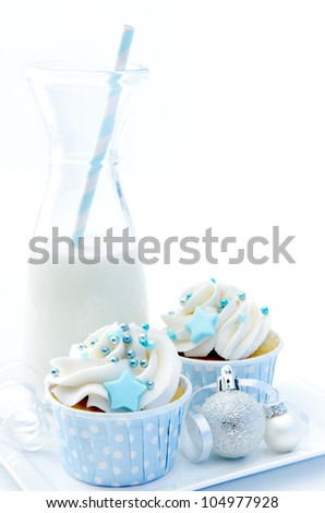 White christmas cupcakes with silver baubles and a bottle of milk - stock photo