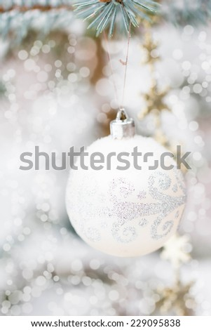 White Christmas decorations and snowy blue spruce, bokeh effect, selective focus for the center of decorations