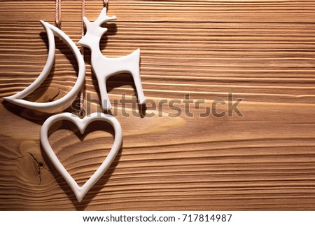 White Christmas decorations hanging on wooden wall. Background with space for text.