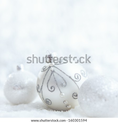 White Christmas ornaments on a snowy surface. - stock photo