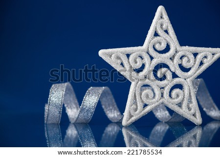 White christmas star with silver ribbon on blue background with space for text. Xmas holiday theme. - stock photo