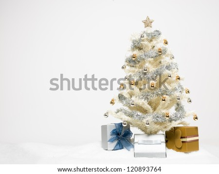 white christmas tree beautifully decorated with shiny golden and silver decorations surrounded with colorful gift boxes and artificial snow isolated on white background