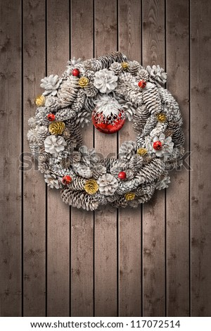 White Christmas wreath on brown wooden door background - stock photo
