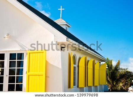 White church building with bright yellow window shudders in Hope Town, Abaco, Bahamas - stock photo