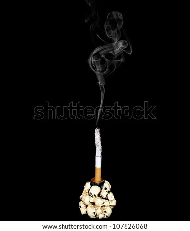 White cigarette in a candlestick decorated with human skulls - stock photo
