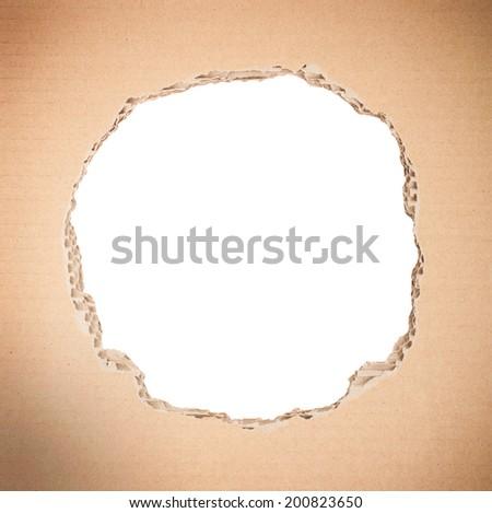 White circle shape breakthrough in beige cardboard - stock photo