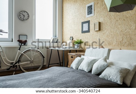 White city bicycle in bedroom with wooden wall - stock photo