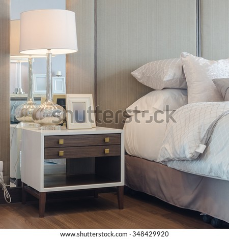 white classic lamp with glass vase of flower on table side in bedroom - stock photo