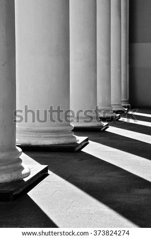 White classical columns with contrasting shadows in perspective. - stock photo