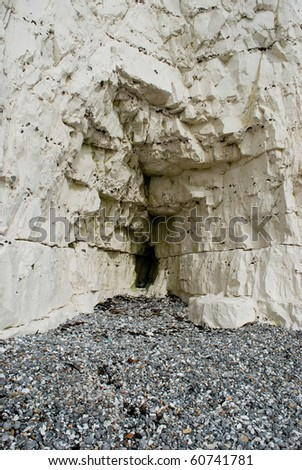 White cliff with small cave as background