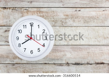 white clock on the light brown grunge wood plank background texture with copy space from top view/ Business time, Breakfast time,Time to Start - stock photo