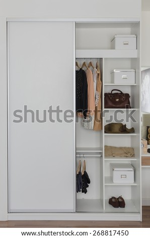 white closet with clothes and accessories at home - stock photo