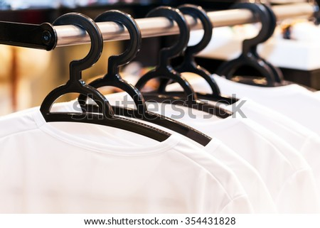 White clothes hanging on hangers in a store for sale
