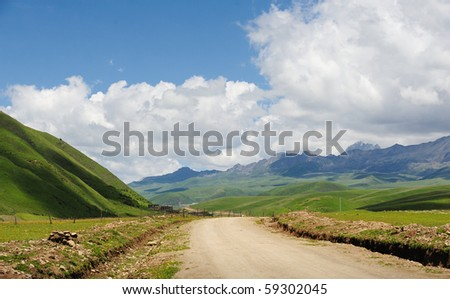 white cloud,mountain,grassland and clay road. - stock photo