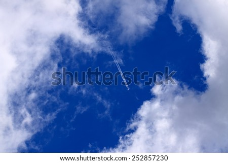 White clouds against blue sky seeing an airplane - stock photo