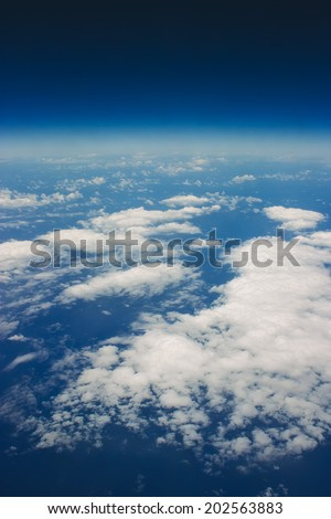 White clouds in a blue sky. Aerial view from airplane.