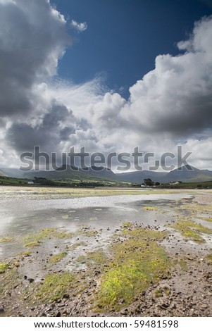 White clouds in blue sky over Irish hills and estuary at Dingle peninsula Kerry district Ireland - stock photo