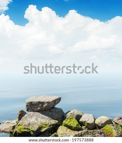 white clouds in blue sky over water. soft focus on stones
