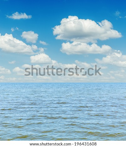 white clouds in sky over blue sea - stock photo