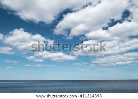 White clouds over still Baltic sea. - stock photo