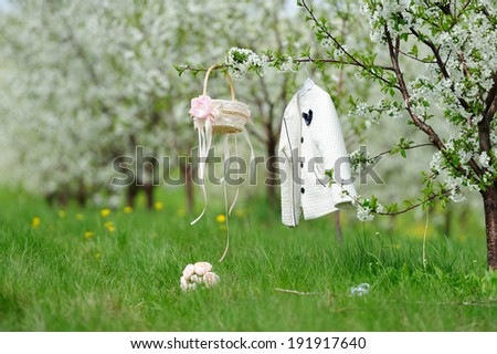 white coat on the rack, basket and bouquet of flowers in the garden with white bloom - stock photo