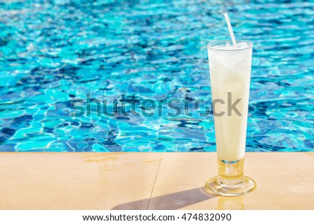 White cocktail beside swimming pool. Blurred water on the background. Travel, summer, lifestyle concept. Text space