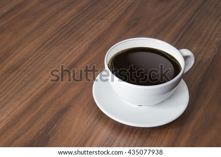 white coffee cup and hot espresso coffee on wooden table. - stock photo