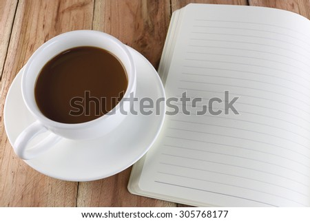 White coffee cup and notebook on wood background.