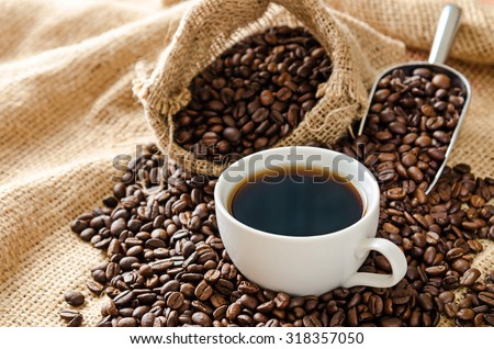 white coffee cup and roasted coffee beans around
