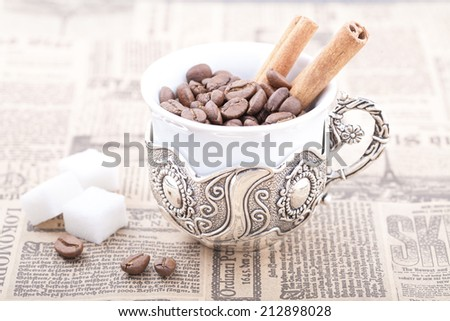 White coffee cup filled with coffee beans on newspaper with cinnamon - stock photo