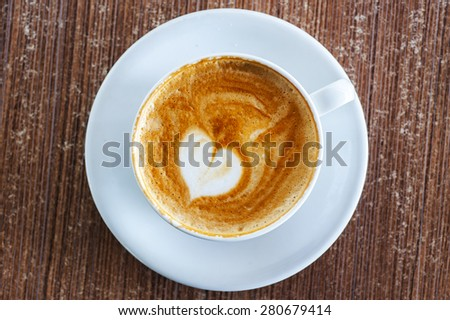 White coffee cup on a saucer with a heart shape in the latte foam - stock photo