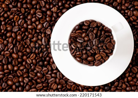 White coffee cup on coffee beans - top view - focus on cup