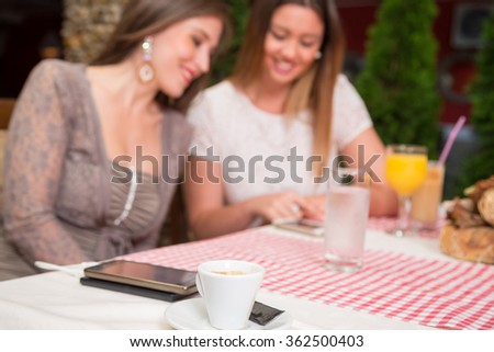 White coffee cup on table in restaurant. Smiling women are using cell phone in the background.