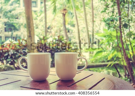White coffee cup on table with outdoor view - Vintage Filter
