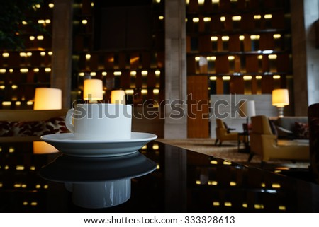White Coffee cup on the table in lounge bar background.