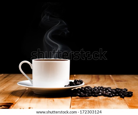 White coffee cup on wooden table and dark background - stock photo