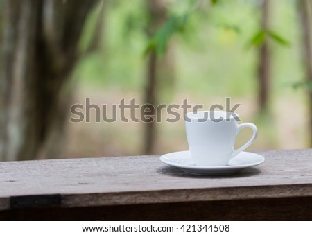 white coffee cup on wooden table, relaxation forest background scene
